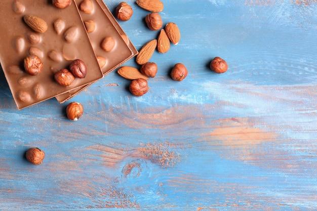 Сладкий шоколад с орехами на деревянном столе