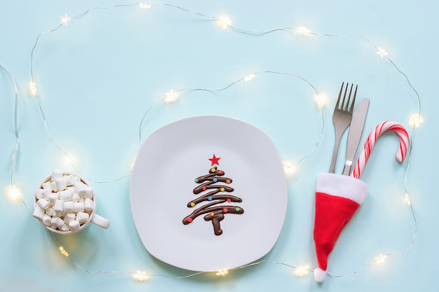 Sweet christmas tree made of chocolate, cutlery and cup of cocoa marshmallow and light bulbs garland