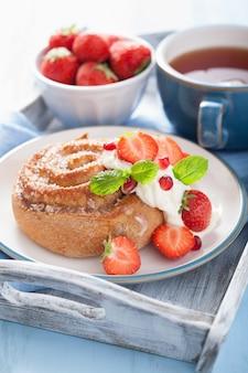 아침에 크림과 딸기와 달콤한 계 피 롤
