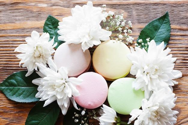 프랑스 전통 쿠키의 달콤한 근접 촬영 사진입니다. 나무 테이블에 꽃과 함께 사랑스러운 마카롱.