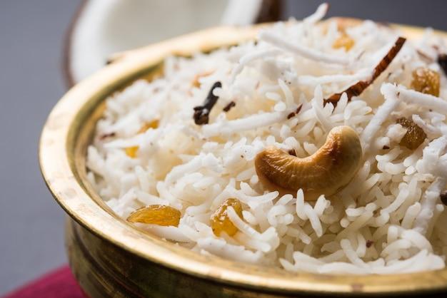 달콤한 코코넛 라이스 또는 마라티의 narali bhat, 캐슈, 정향 및 마른 과일로 장식되어 황동 그릇에 담겨 분위기 있는 배경 위에 제공됩니다. 선택적 초점