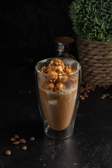 Sweet coffee with caramel popcorn in a transparent two-layer thermo glass.