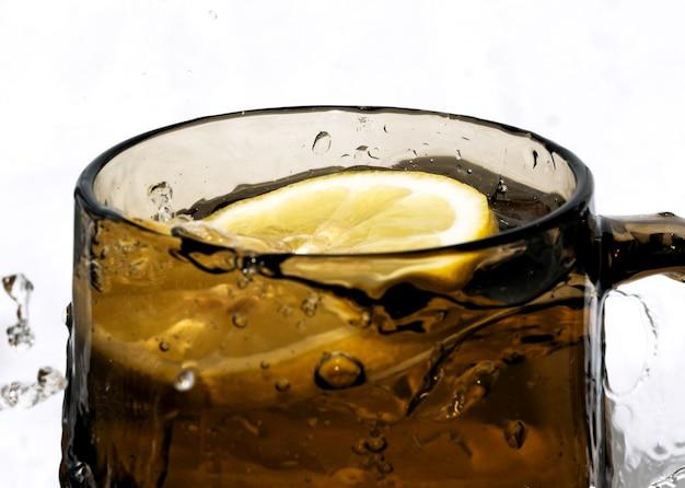 白い背景のクローズアップに水しぶきと暗いガラスの甘い冷たいレモネード