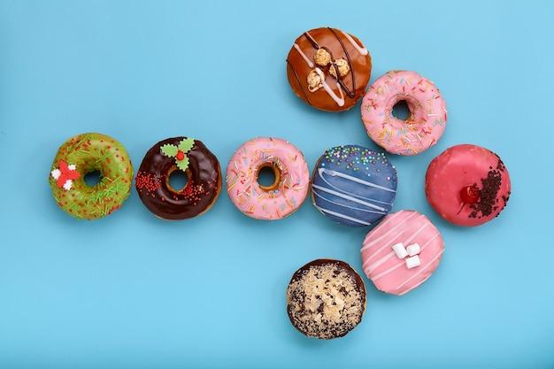 Сладкие цветные пончики на синем фоне, выложенные в виде различных геометрических фигур, стрелки, квадрата, линии, треугольника, вид сверху