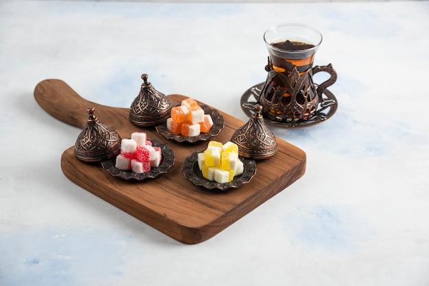 Dolci caramelle colorate su tavola di legno accanto a tè caldo fresco