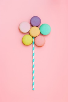 Sweet and colorful french macaroons or macaron on pink background, dessert. minimal concept.