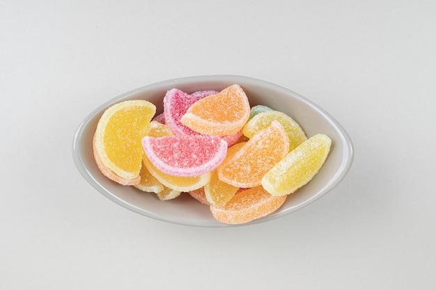 Caramelle di gelatina colorate dolci in una ciotola sulla superficie beige