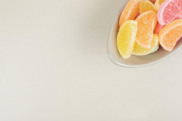 ベージュの表面のボウルに甘いカラフルなゼリーキャンディー