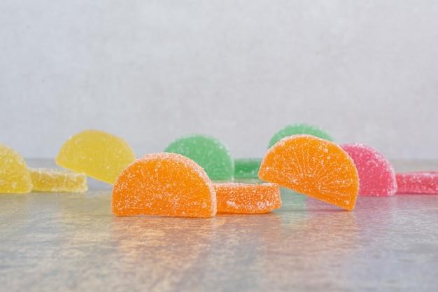 大理石の背景に甘いカラフルなゼリーキャンディー