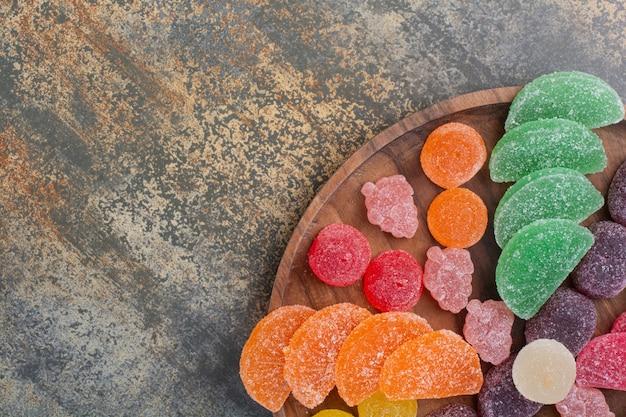 Сладкие красочные конфеты желе на деревянной тарелке. фото высокого качества
