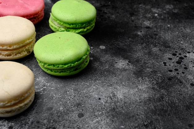 Sweet colorful macarons set, on black dark stone table background, with copy space for text