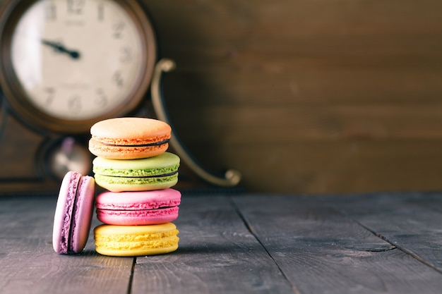 Sweet and colorful macaroon cookies tower on dark background