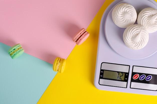 カラフルなパステルカラーの甘いカラフルなマカロンとキッチンのメレンゲ