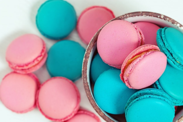 Sweet colorful macaroons close up in bowl on wooden white table. t