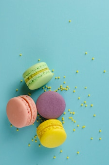 Sweet colorful macaroons decorated with sprinkles on pastel blue