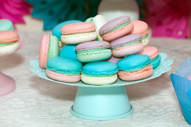 Сладкие красочные миндальное печенье в вазе на столе.