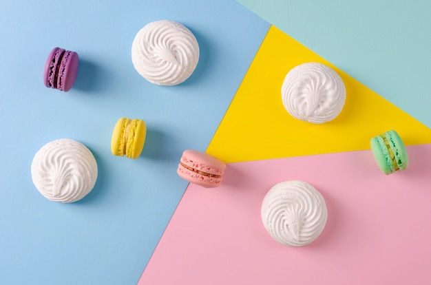 Sweet colorful macaroons or macarons on colorful pastel colors