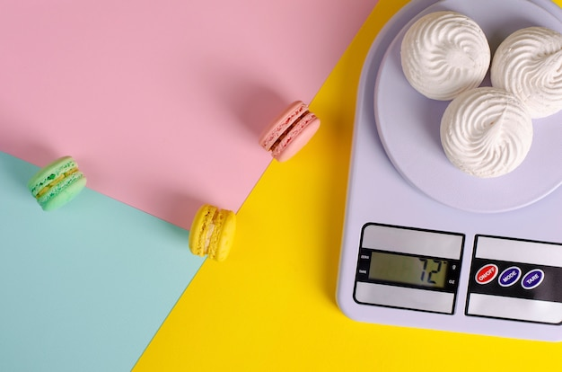 Sweet colorful macaroons and meringues on kitchen scales on colorful pastel colors