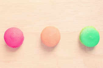 Sweet colorful macaroons on wood with retro filter effect