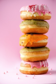 Sweet and colourful doughnuts on pink background. fresh baked donuts. copy space.