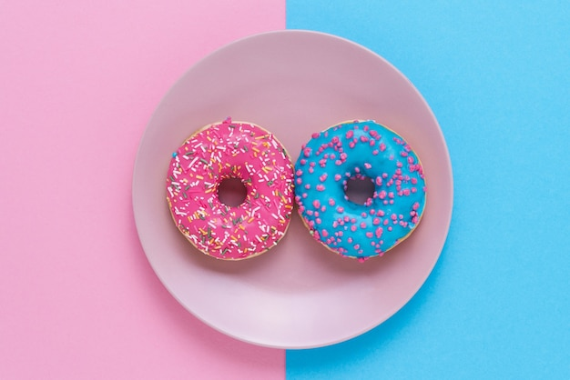 Sweet and colourful doughnuts on the plate on pink-blue backdrop. top view, copy space.