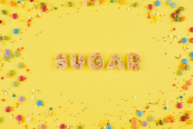 다채로운 뿌리와 밝은 노란색 배경에 달콤한 쿠키 단어 설탕, 위에서 볼