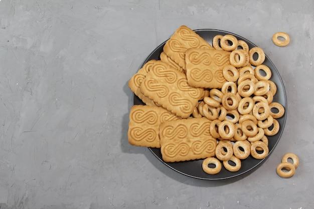 회색 배경에 검정 접시에 차를 위한 달콤한 쿠키와 베이글
