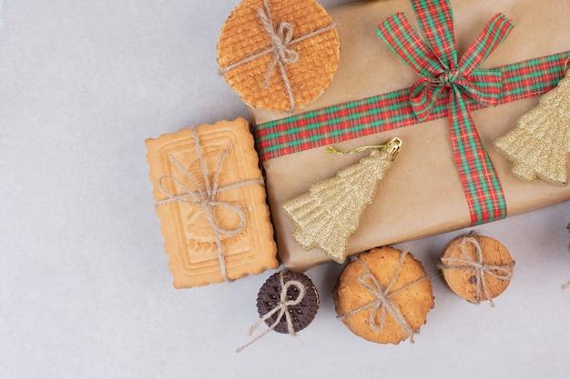 Сладкое печенье в веревке с подарком и рождественской золотой игрушкой на белой поверхности