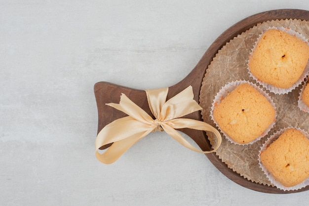 리본으로 장식 된 나무 접시에 크림과 함께 달콤한 쿠키.