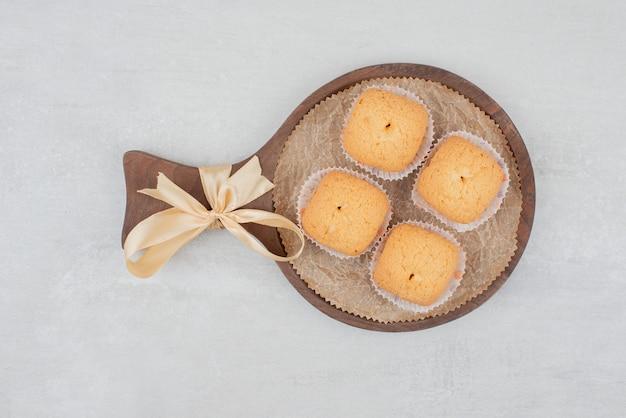 Сладкое печенье со сливками на деревянной тарелке