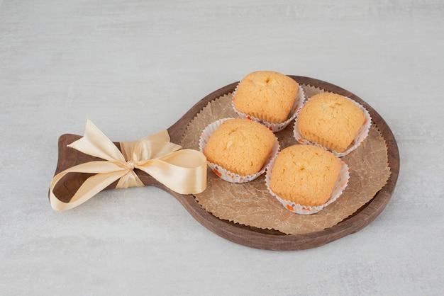 Biscotti dolci con crema sul piatto di legno decorato con nastro.