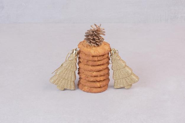 白いテーブルの上の金色のクリスマスのおもちゃと甘いクッキー。