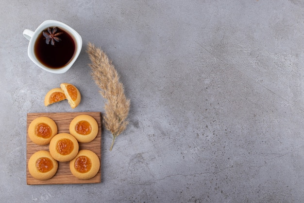 石のテーブルの上に置かれたジャムと紅茶のカップと甘いクッキー。