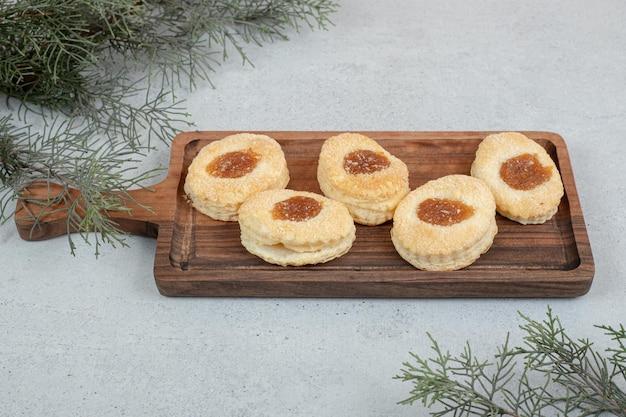 木製のまな板にジャムと甘いクッキー。