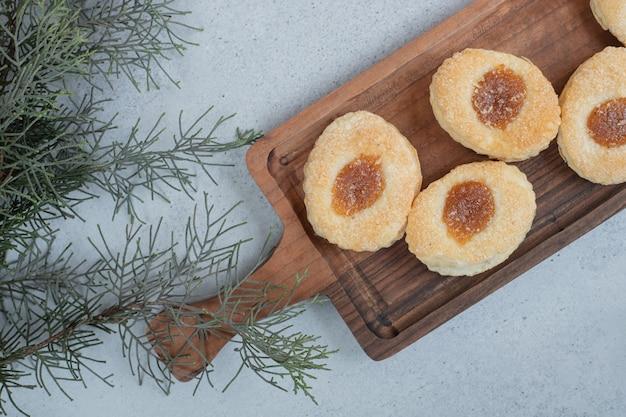 나무 커팅 보드에 잼이 있는 달콤한 쿠키