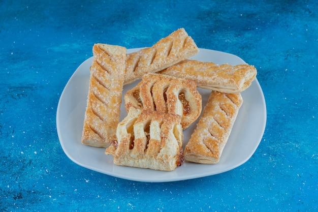 Biscotti dolci con marmellata sul piatto, su sfondo blu. foto di alta qualità