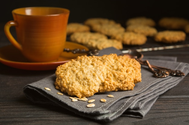 Sweet cookies with oat on tissue with tea or coffee
