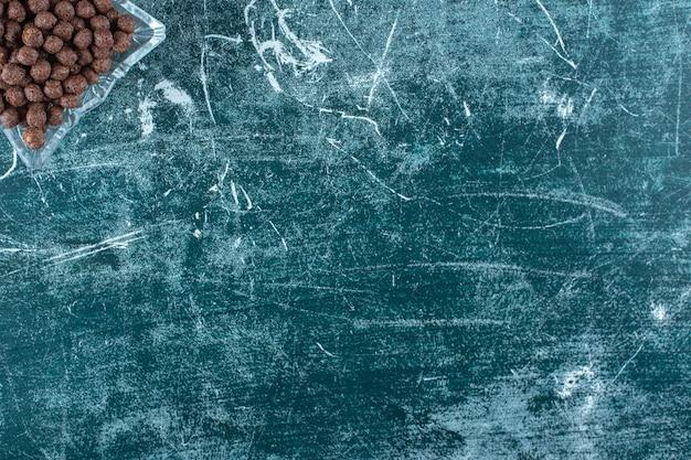 Palline di mais dolce in una ciotola di vetro, sul tavolo blu.