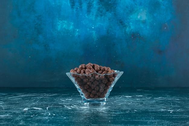 Сладкие кукурузные шарики в стеклянной миске, на синем фоне. фото высокого качества