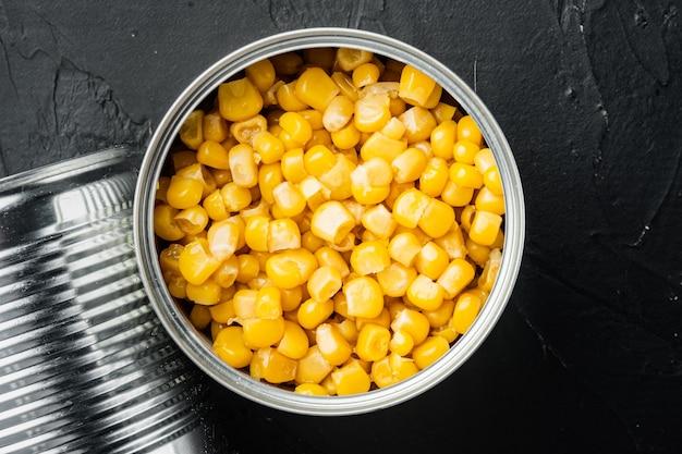 ブリキ缶のスイートコーンの穀物、黒いテーブル、上面図フラットレイ