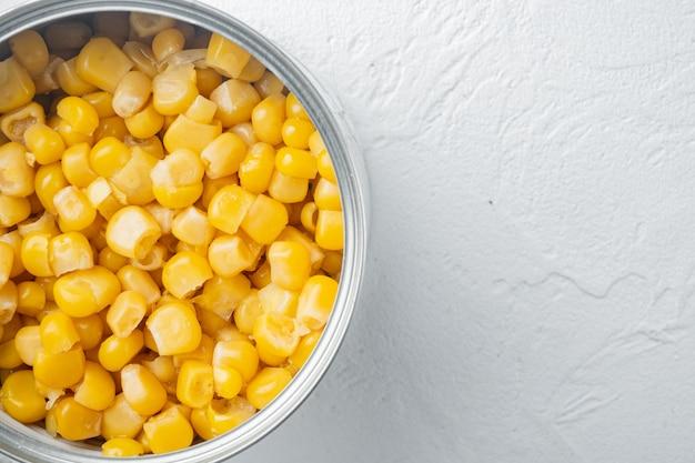 ブリキ缶のスイートコーンの穀物は白い上面図フラットレイ