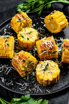 Sweet corn grilled on fire with parmesan and parsley. organic farm vegetables. top view