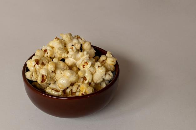 Попкорн сладкой кукурузы в коричневом горшке с пространством для текста.