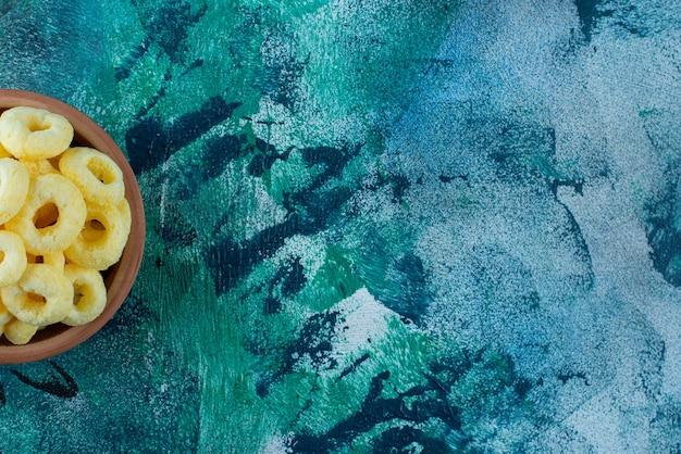 大理石のテーブルの上に、粘土のボウルにスイートコーンの指輪。