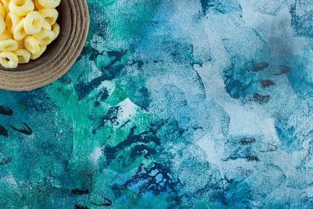 大理石のテーブルの上に、トリベットの木製のボウルにスイートコーンの指輪。