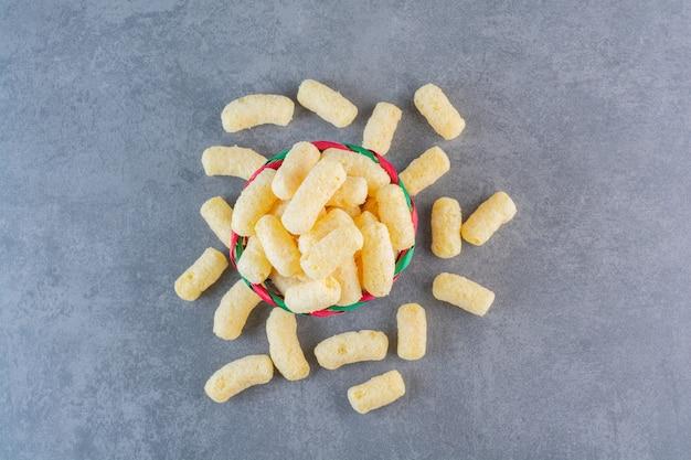 Bastoncini di mais dolce in una ciotola, sulla superficie di marmo