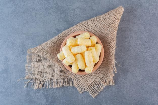 Bastoncini di mais dolce in una ciotola, sulla consistenza, sulla superficie di marmo