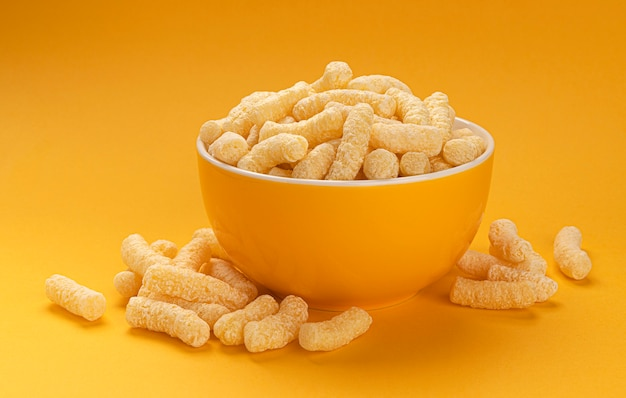 Сладкие кукурузные палочки в миске, изолированные на желтом