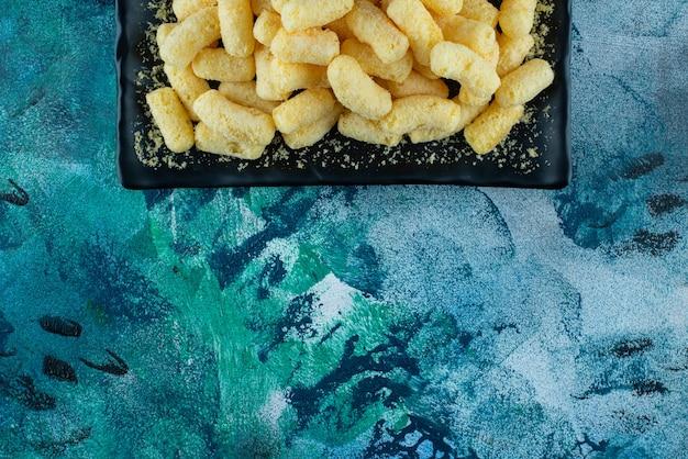 Bastoncini di mais dolce su un piatto, sul tavolo blu.