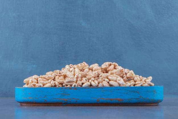 大理石のテーブルの上に、木の板に甘いコーンフレーク。 無料写真